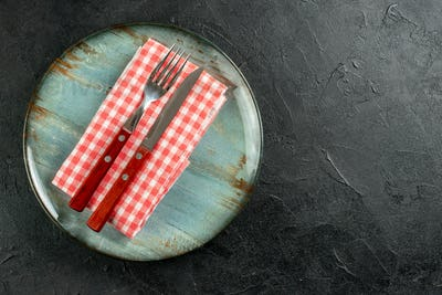 top view fork and knife on red white checkered napkin on round plate on dark table with copy place