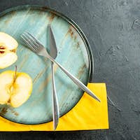 top view apples cut in half crossed fork and dinner knife on round platter yellow napkin on black