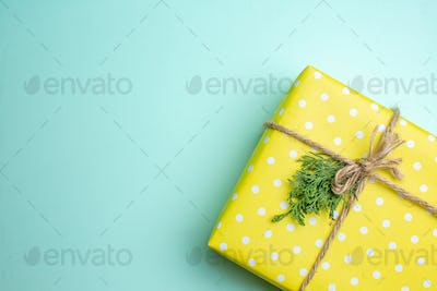 Half shot of Christmas background with yellow gift box on pastel green background