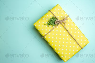 Overhead view of Christmas background with yellow gift box on pastel green background