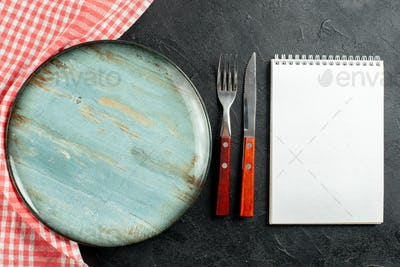 top view fork and knife red white checkered napkin round plate notebook on dark table