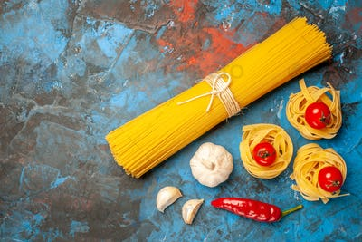 Above view of vermicelli noodles tied with ropes and peppers garlic on blue background
