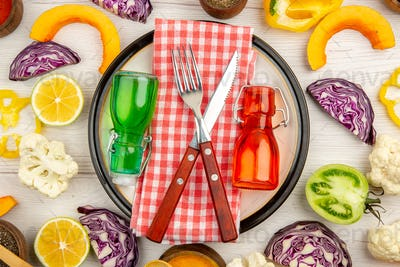 top view crossed fork and knife on napkin green and red bottles on white platter chopped vegetables
