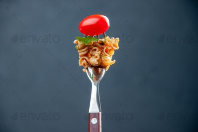 front view rotini pasta with cherry tomato on fork on grey isolated background with free space