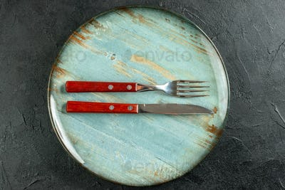 top view horizontal fork and knife on round plate on dark ground stock photo