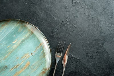 top half view fork and knife round plate on black table free space