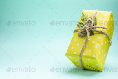 Close up view of xsmas background with yellow gift box on pastel green background