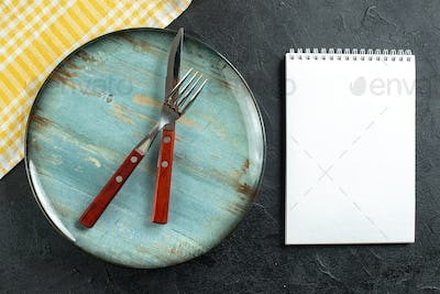 Horizontal view of meal cutlery in cross on a blue plate and yellow stripped towel next to notebook