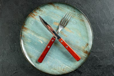 top view crossed fork and knife on round plate notebook on dark ground