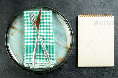 top view crossed steel dinner knife and fork on green and white checkered napkin on platter