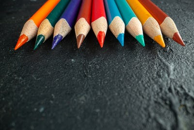 front close view colorful pencils lined on dark background drawing color photo art school