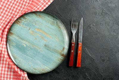 top view fork and knife red white checkered napkin round plate on dark table with copy space