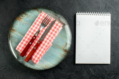 top view fork and knife on red white checkered napkin on round plate notebook on dark table