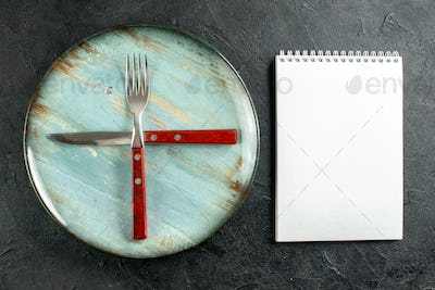 top view crossed fork and knife on round plate notebook on dark ground stock photo