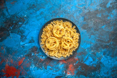 Top view of dinner preparation with pasta noodles on a black plate on blue background