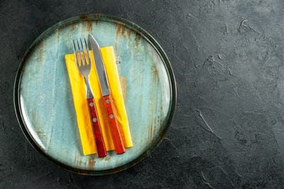 top view yellow napkin knife and fork on plates on black table with free space
