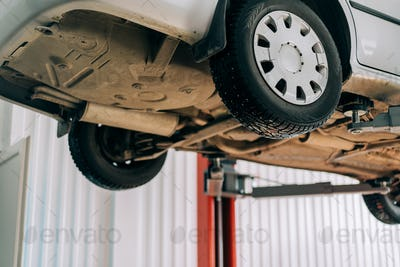 Car lifted on car lift for routine maintenance