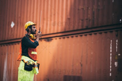 Engineering Foreman using walkie talkie to management and control loading containers