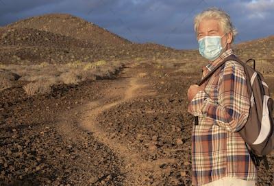 Elderly man walking in a path in an arid landscape enjoying nature. Cloudy sky and mountains