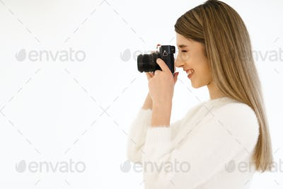 Smiling woman holding camera on white background