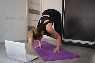 young woman doing asana at home on yoga mat in front of laptop