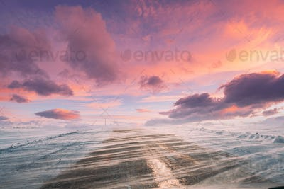 Snow-covered Open Slippy Road During A Snowstorm Blizzard In Winter. Altered Colorful Sunset Sunrise