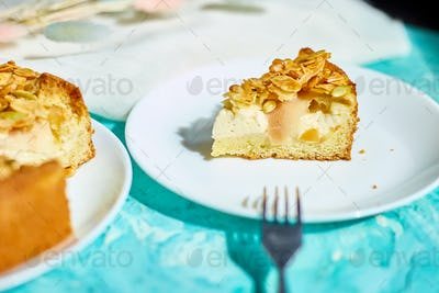 Piece of apple or pear pie, tart with caramel nuts on blue table with sunlight