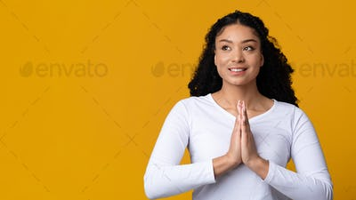 Young african american woman praying, clasping hands together and looking away