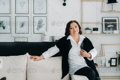 portrait of a business woman in a white shirt with a vest sitting on a sofa in the interior