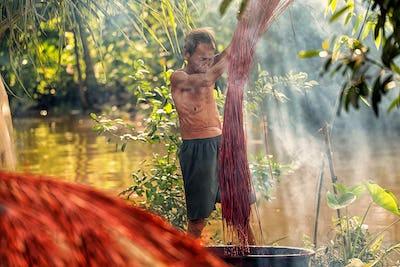 Vietnamese Old man craftsman Dyeing the traditional vietnam mats in the old traditional
