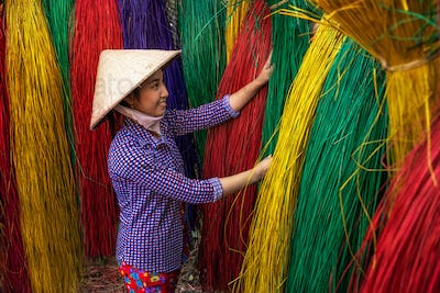 Vietnamese female craftsman drying traditional vietnam mats in the old traditional village