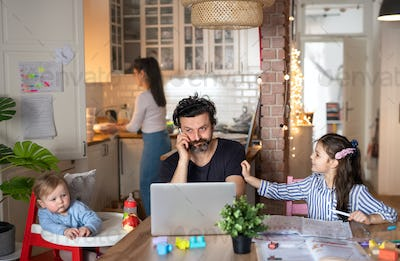 Father with small daughters in kitchen, distance learning, home office and schooling concept