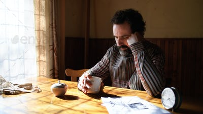 Portrait of unhappy poor mature man reading newspapers indoors at home, poverty concept