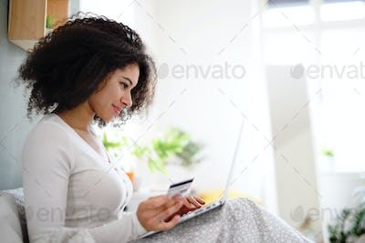 Portrait of young woman with laptop indoors on bed, online shopping concept
