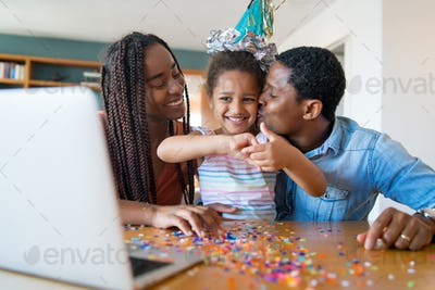 Family celebrating birthday on a video call.