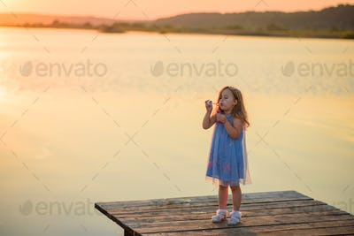 A little girl blows bubbles on the pier near the lake.