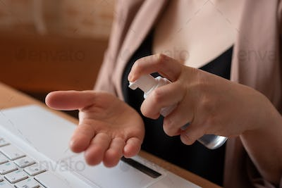 A female freelancer rubs her hands with a hand sanitizer.