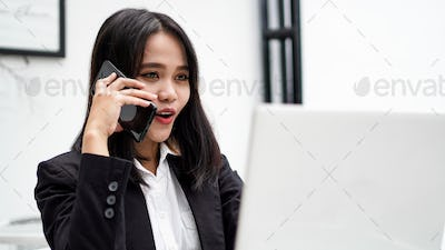 Asian young business woman working on computer and talking on smartphone in office