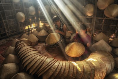 Two Vietnamese sisters craftsman making the traditional vietnam hat in the old traditional