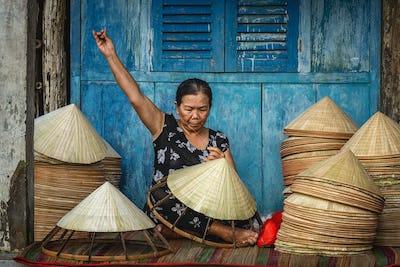 Vietnamese Old woman craftsman making the traditional vietnam hat in the old traditional