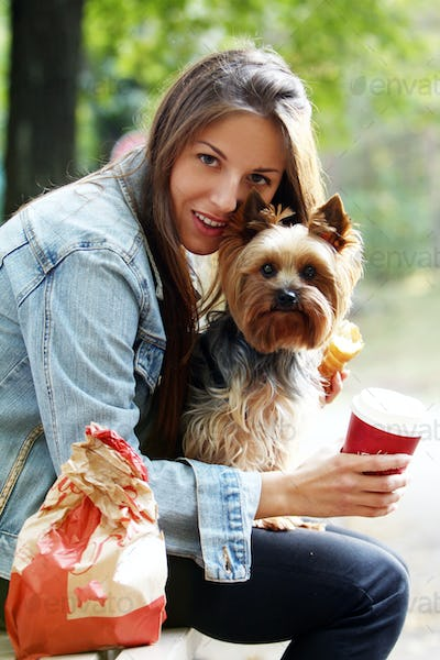 Woman have lunch while strolling with her dog