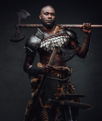 Black skinned antique soldier with dual axes looking at camera
