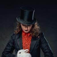 Caucasian professional illusionist and white little rabbit in dark background
