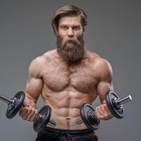 Masculine guy with sportive body holding dumbells in gray background