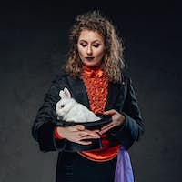 Beautiful white rabbit sits in top hat and female artist holding it