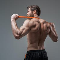 Fitness instructor poses in gray background with rubber bands