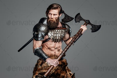 Proud viking with two axes and grimy face prepared to fight