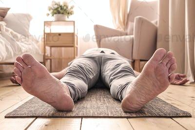 Caucasian man meditating on a wooden floor and lying in Shavasana pose