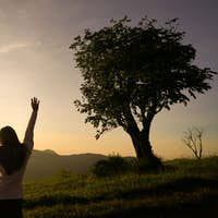 woman open arms at sunrise