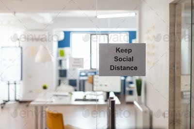 Keep Social Distance sign on glass wall in empty office